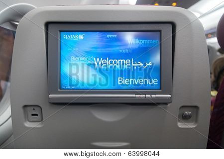 DOHA, QATAR - FEBRUARY 18, 2014: Economy class seat with entertainment system onboard. Qatar Airways Economy Class was named best in the world in the 2009 and 2010 Skytrax Awards.