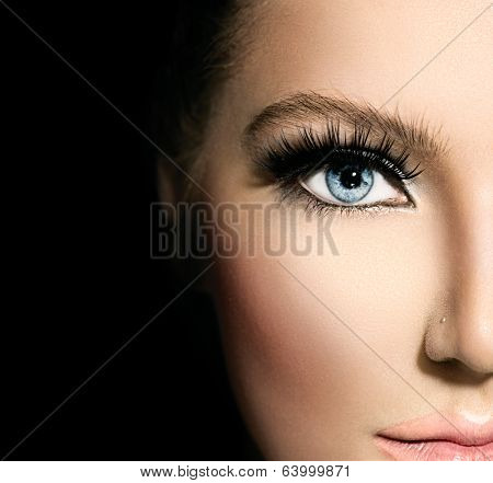 Beauty makeup for blue eyes. Part of beautiful face closeup. Perfect skin, long eyelashes. Make up concept. isolated on black background poster
