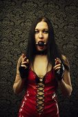 Pretty girl in red latex dress with mouth gag stands in an empty room poster