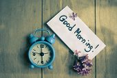 Good morning note lilac flowers and old-styled clock on the wooden table poster
