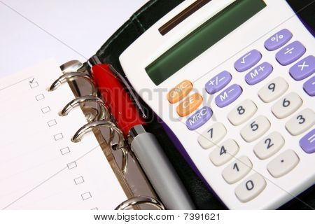 White Calculator And A Red Pen On An Organizer