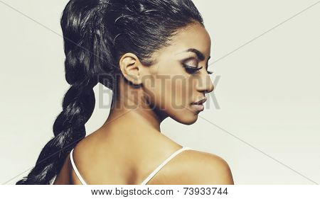 Profile of beautiful young woman's face and braided ing hair