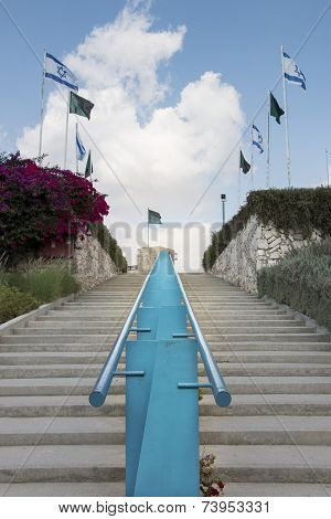A staircase with blue rail leading to the Latrun Museum Courtyard poster
