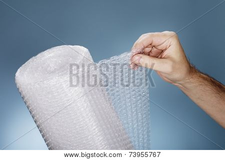 Man holding a roll of plastic bubble wrap. poster