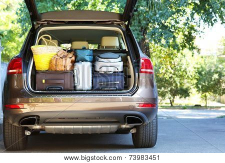 Suitcases and bags in trunk of car ready to depart for holidays poster