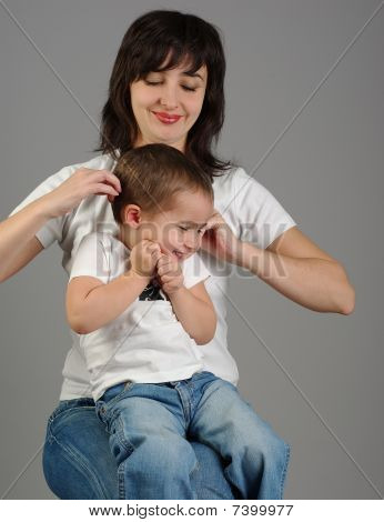 Mother titillates her son on gray background poster