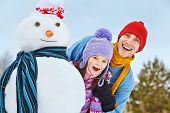 funny dad and daughter with a snowman. Family walking outdoors in winter poster