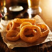 crispy onion rings with ketchup on parchment paper poster