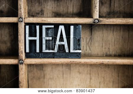 "The word ""HEAL"" written in vintage metal letterpress type in a wooden drawer with dividers. poster"