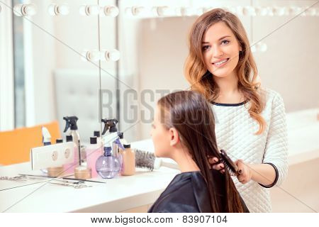 poster of I love my job. Beautiful hairdresser doing hairstyle to her client and smiling at camera while standing on the background of a professional hairdressing salon
