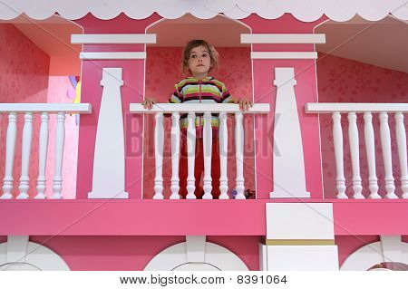 Little Girl Standing On Pink Childish Balcony And Looking Into The Distance