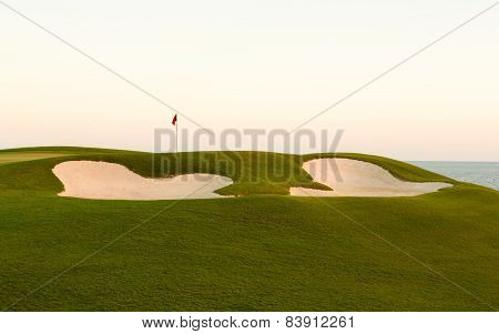Sand Bunker In Front Of Golf Green And Flag