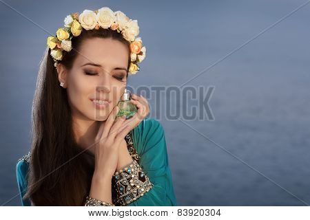 Young Woman With Floral Wreath Holding Perfume Bottle in Seaside Landscape