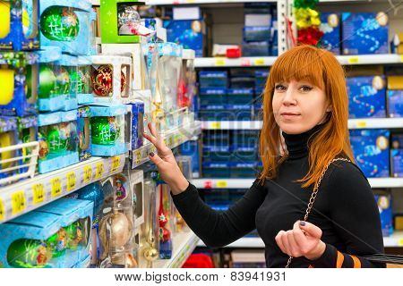 Girl In Shop Chooses Christmas Decorations