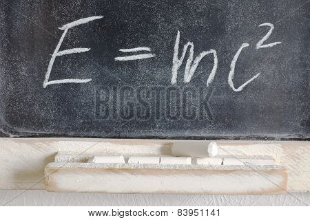 poster of well-known physical formula written in chalk on blackboard
