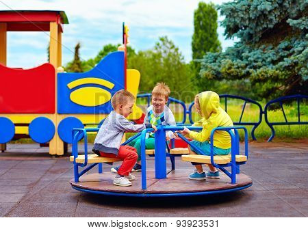 Three Little Friends, Kids Having Fun On Roundabout At Playground