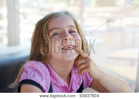 Blond happy kid girl showing her indented teeth portrait