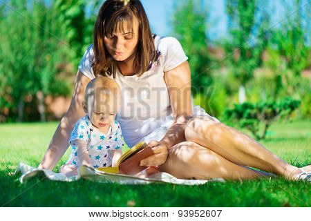 Young Mother Reading Book To Her Little Son