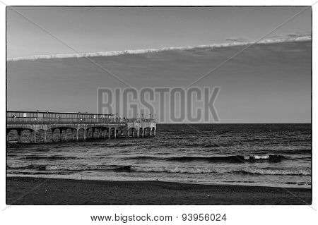 A Black And White Image Of Sunset Light Of A Pier Looking Towards The Sea At The Beach With Sand  An