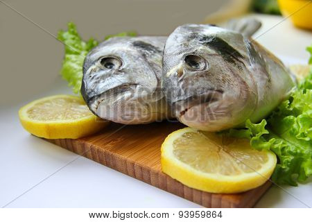 Fresh Dorado On Chopping Board With Lemon And Vegetables