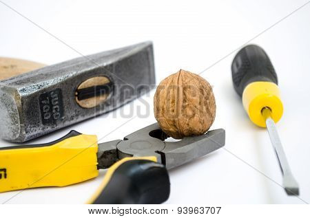 Toughie Clamped With Pliers Against A Background Of A Hammer And Screwdrivers