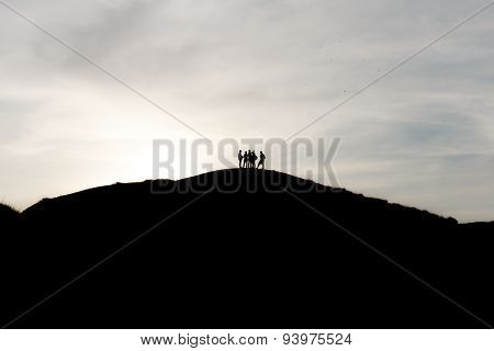 Silhouettes Of Tourists On Mountains
