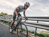 Cyclist in maximum effort in a road outdoors poster