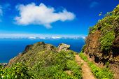 Pathway or footpath in green mountain or rock and blue sky with clouds and skyline or horizo in Tenerife Canary island Spain at spring or summer poster