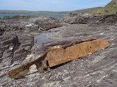 Boat wreckage upon cliff seascape photographed at Polzeath in Cornwall poster