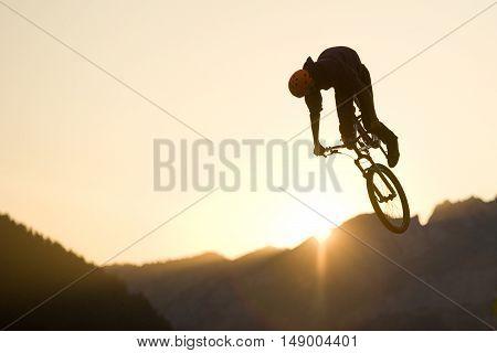 Dirt biker jumping on sunset in mountain