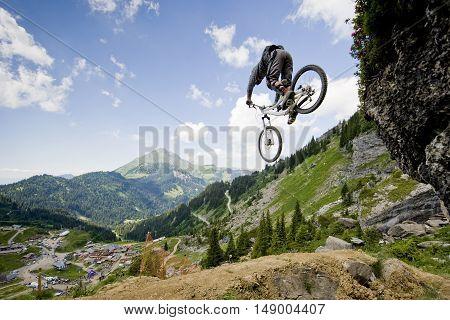 Freeride mountainbiker jumping from a rock on bike