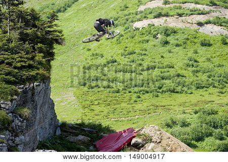 Freeride mountainbiker huge jumping from a rocks