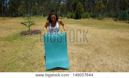 Young latin woman unrolling yoga mat in the middle of the park