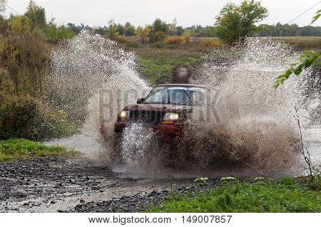 Sport Suv Boosts Water Hurdle Surrounded By Splashes.