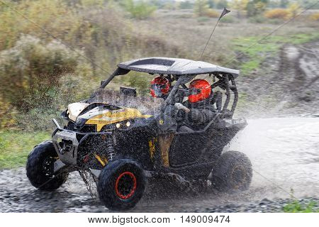 Atv Vehicle Boosts Water Hurdle Surrounded By Splashes.
