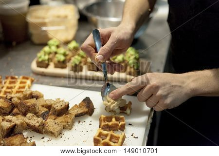 A chef assembles chicken and waffles appetizer for restaurant guests.