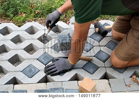 man laying a garden path with grass gray paving blocks and filling
