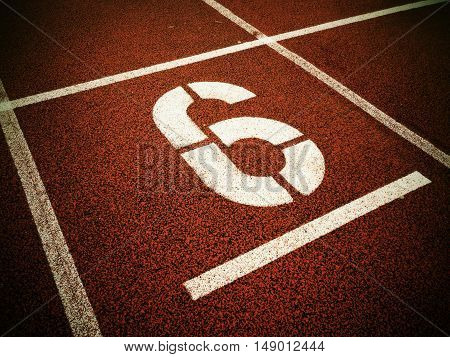 Number Six. White Athletic Track Number On Red Rubber Racetrack