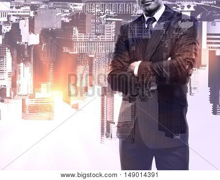 Young businessman with folded arms standing on upside-down city background with abstract sunlight. Double exposure