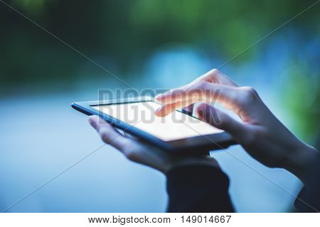 Female hands using tablet on abstract blurry background