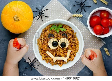 Child eat pasta with sauce in the shape of a smiling vampire face funny dinner or lunch in Halloween style. Creative idea for schoolboy food. Fun with food consept top view