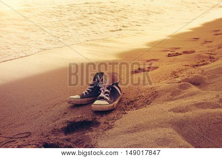 Hipster sneakers in a sea surf on a sand with footprints. Active wild ocean rest vacation and tourism theme
