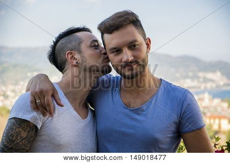 Stylish handsome men walking on sidewalk and kissing. Gay couple outdoor