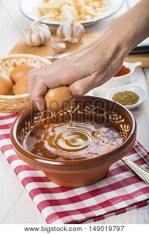 Chef Cracking An Egg On A Garlic Soup