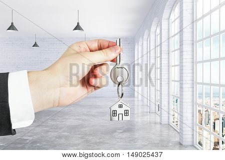 Closeup of businessman hand holding key with house keychain in brick interior. Real estate and mortgage concept