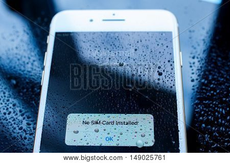 PARIS FRANCE - SEP 26 2016: New Apple iPhone 7 Plus unboxing and testing - no sim card installed under rain drops on screen. New iPhone7 is one of the best waterproof smart phone in the world