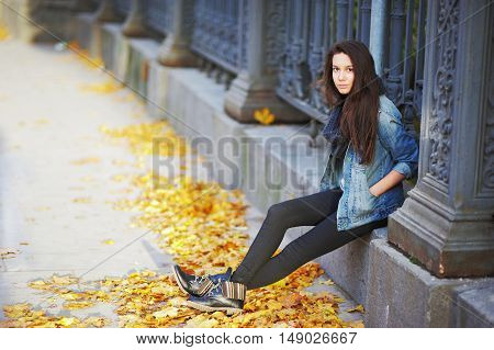 Beautiful long-haired girl in a denim jacket and boots sitting beside a beautiful cast-iron fence in the city center.