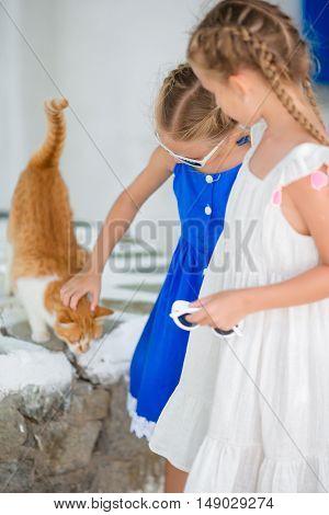 Closeup of Little adorable girls with cat in greek village, Mykonos, Greece