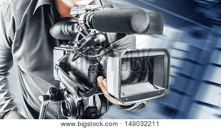 Video operator records the video on the video camera on abstract technological background.