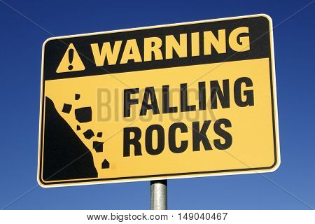 Warning: Falling Rocks sign with a blue sky background.